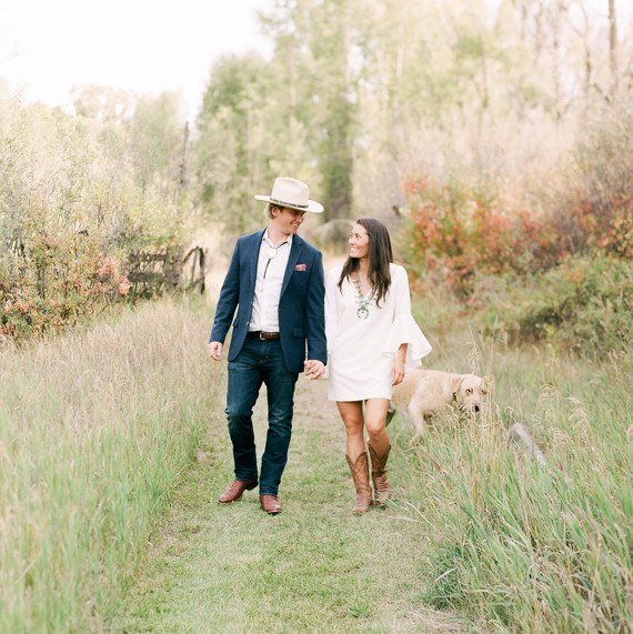 couple walking in field with dog